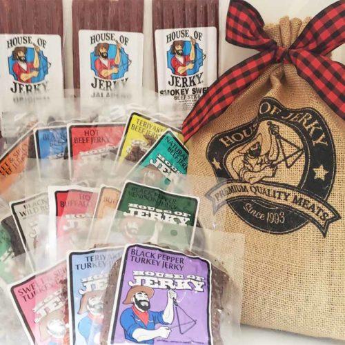 House of Jerky burlap bag with a buffalo ribbon bow with 13 bags of jerky and 3 bags of jerky sticks beside it