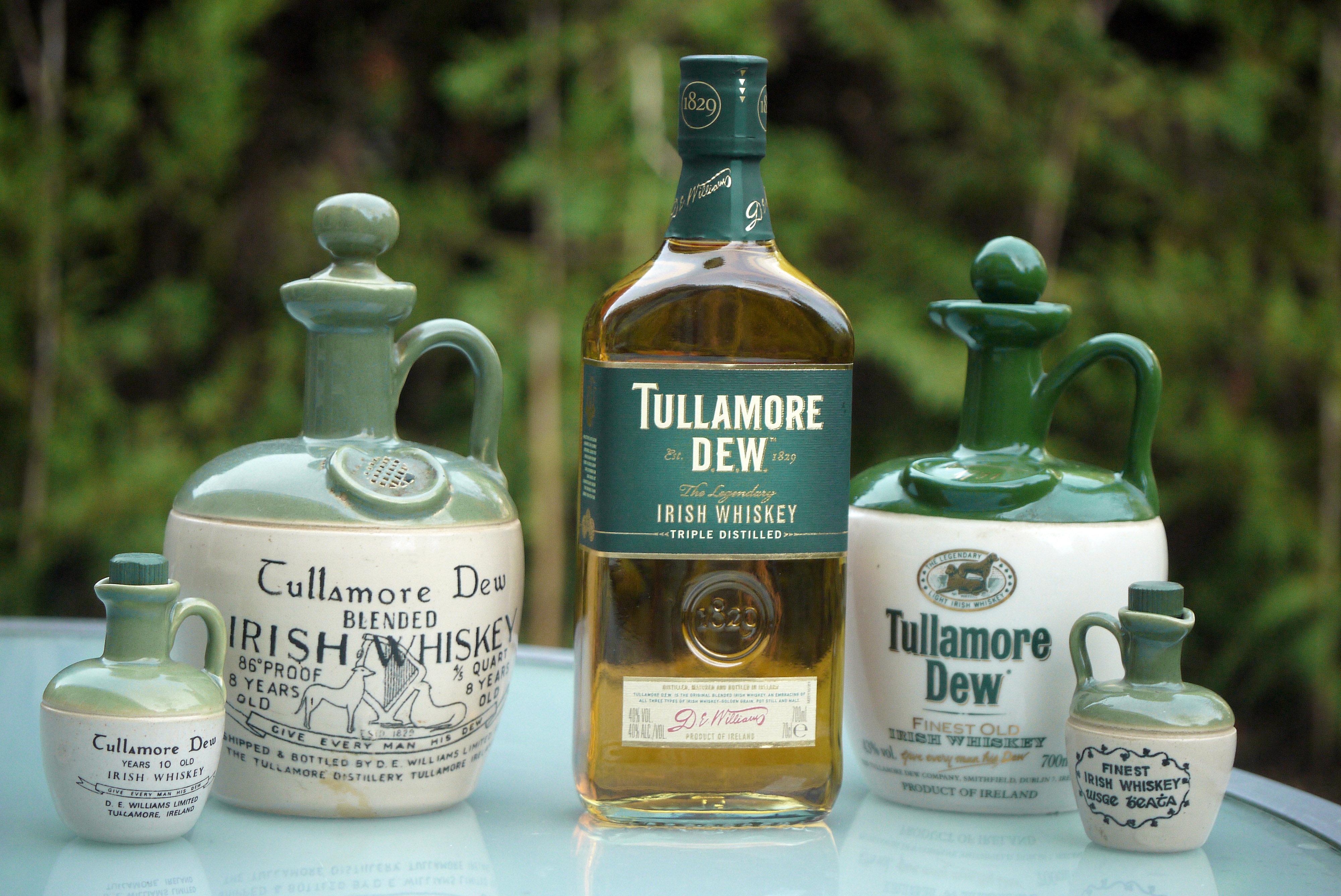 5 different size containers of Tullamore dew Irish Whiskey on a table with trees in the background