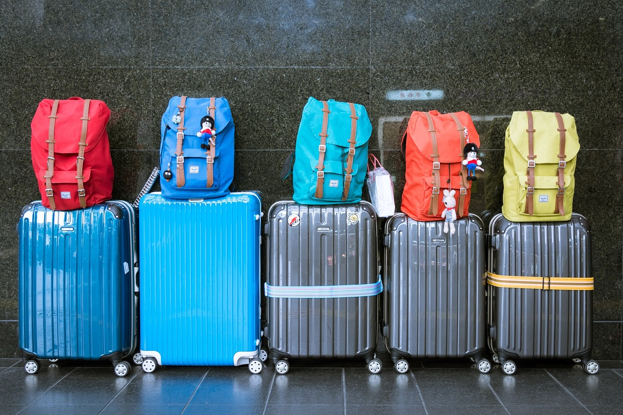 Five beat up suitcases with backpacks on top in front of a marble wall