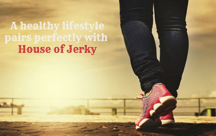 The words A healthy lifestyle pairs perfectly with House of Jerky on the left hand side with a pair of legs wearing jeans and pink shoes on the right an a background of a metal railing an sky background