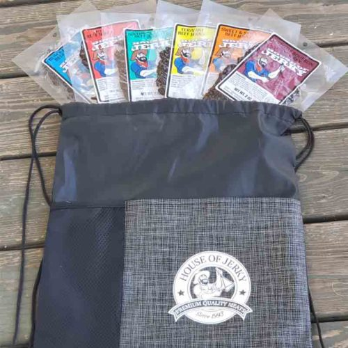 5 bags of jerky at the opening of a house of jerky adventure bag on top of a wood table